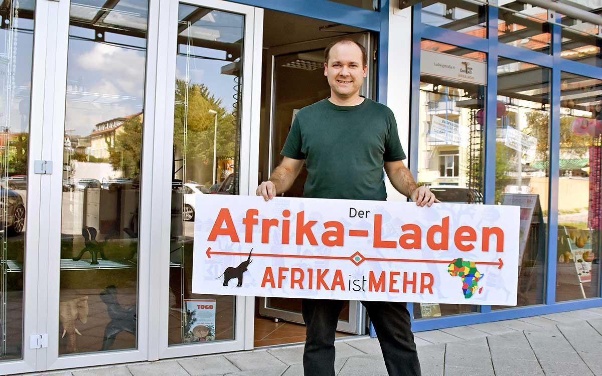 Andy Kopp hält das Schild des neuen Afrika-Ladens hoch